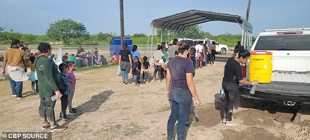 Migrants stand out in the hot Texas sun with little shade and line up to get water as they wait to be processed by border patrol