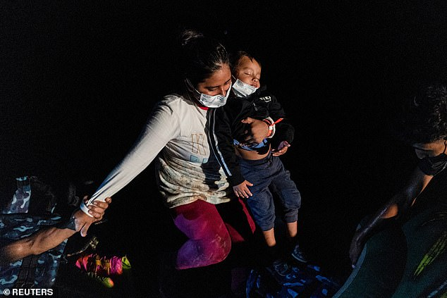Morgan also said agents were instructed to coordinate with Mexico for an increase in security on their side of the border to create the illusion of a decreased migration flow during Mayorkas' trip. Here a migrant mother carries her sleeping child as she prepares to enter the U.s. illegally after crossing the Rio Grande River on August 12