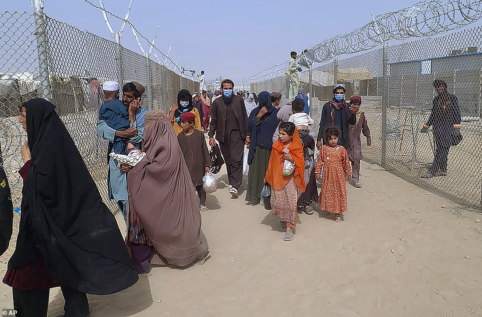 Travelers enter in Pakistan through a border crossing point in Chaman, Pakistan, Monday, Aug. 16, 2021. A special flight of Pakistan's national airline PIA has arrived in Islamabad carrying 329 passengers from Kabul, and another carrying 170 people will arrive later today