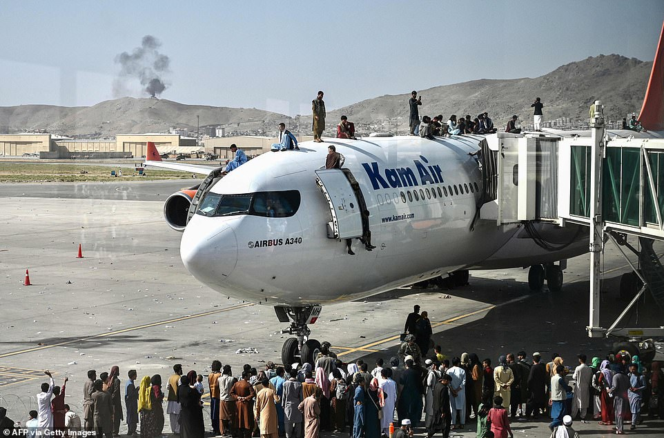 Pictured: Afghan people climb atop a plane as they wait at the Kabul airport in Kabul on August 16, 2021