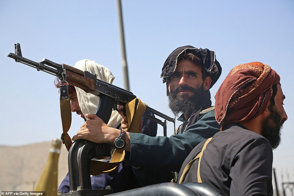 Pictured: Three taliban fighters, one of which is shown holding an AK47 - stand on a vehicle along the roadside in Kabul on August 16, 2021