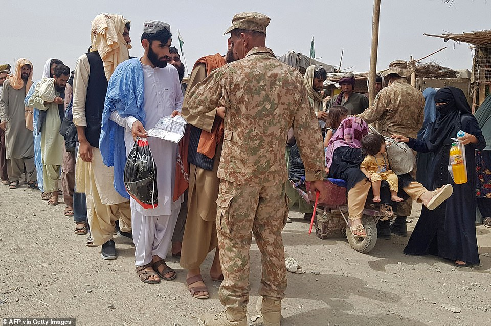 Pictured:Pakistan's soldiers check the documents of stranded Afghan nationals wanting to return to Afghanistan at the Pakistan-Afghanistan border crossing point in Chaman on August 16, 2021