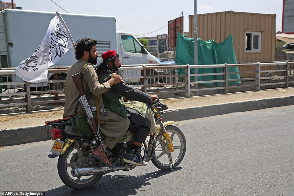 Taliban fighters ride through the city of Kabul on Monday, after a stunningly swift end to Afghanistan's 20-year war, as thousands flee