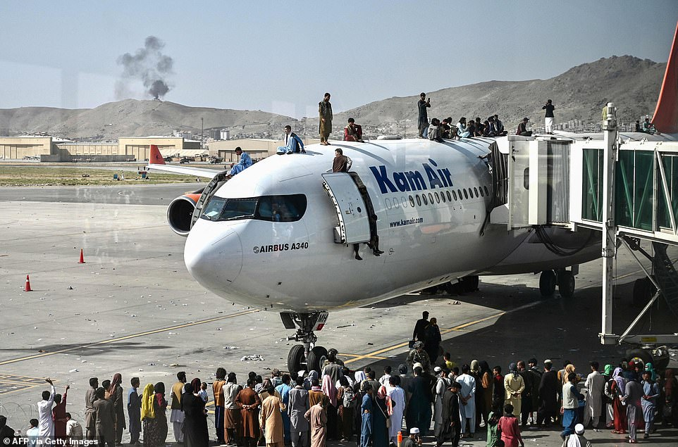 Afghan people climb atop a KamAir plane grounded at Hamid Karazi airport as they wait at the Kabul airport in Kabul on Monday