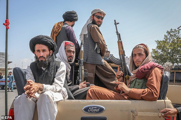 Taliban fighters are seen on the back of a vehicle in Kabul on Monday. Cheney criticized the Trump administration for strengthening the Taliban by negotiating a 'surrender agreement' with them