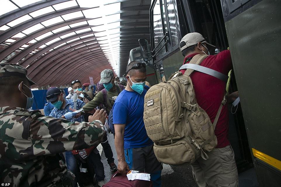 Nepalese people evacuated from Afghanistan arrive via Kuwait at the Tribhuvan International Airport in Kathmandu