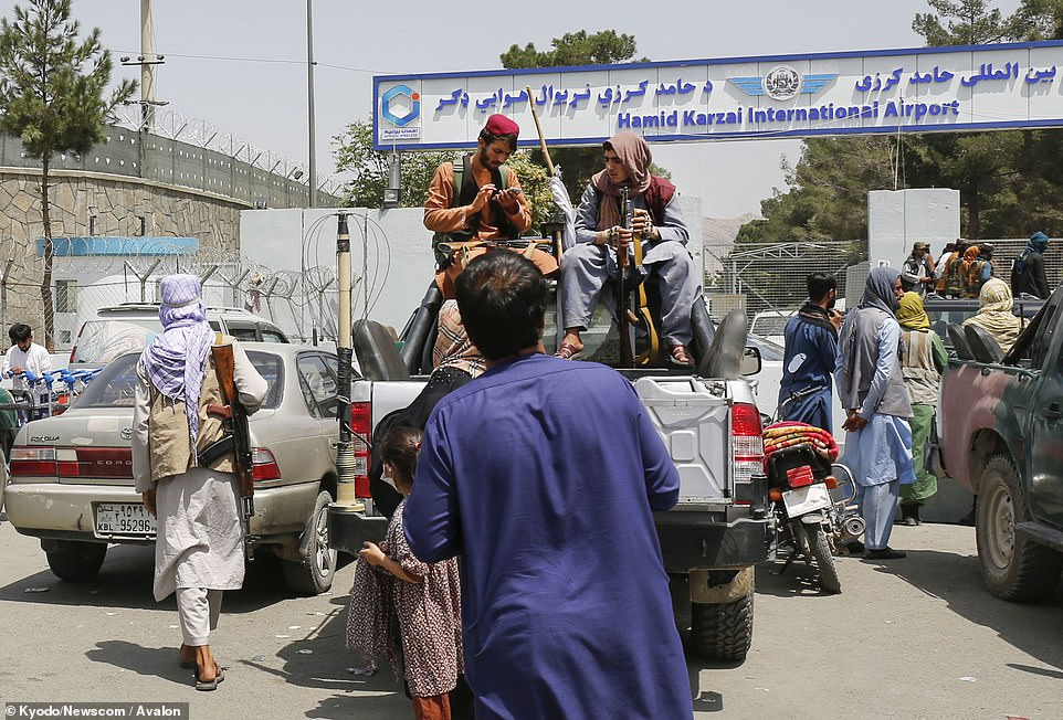 Taliban soldiers at the entrance of Afghanistan's international airport in Kabul today. UK military chiefs admit that the new regime now has total control of access to the airport