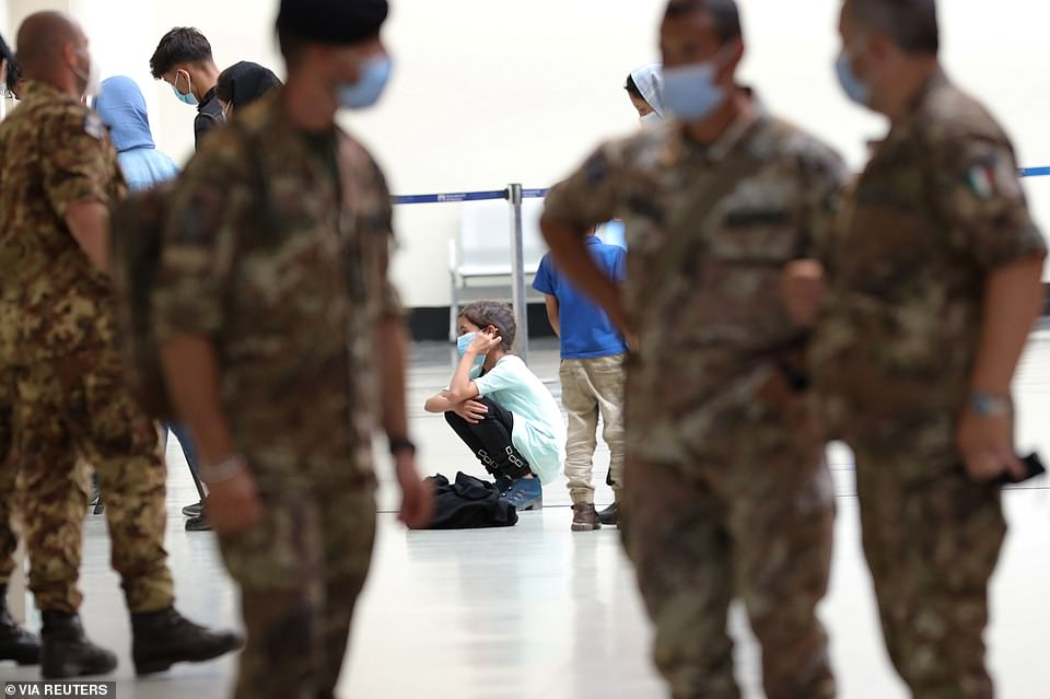 An Afghan girl crouches on the floor of Rome'sFiumicino airport after being evacuated from the country