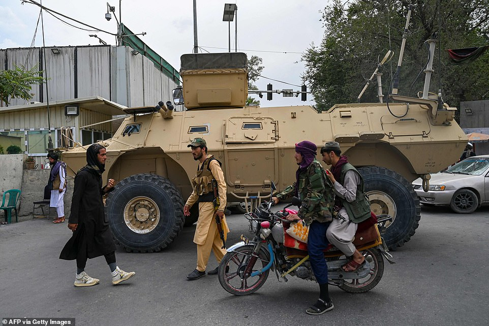 Taliban fighters patrol along a street in Kabul on Tuesday in a US-issued APC, as the Taliban moved to quickly restart the Afghan capital and told government staff to return to work following their stunning takeover of Kabul