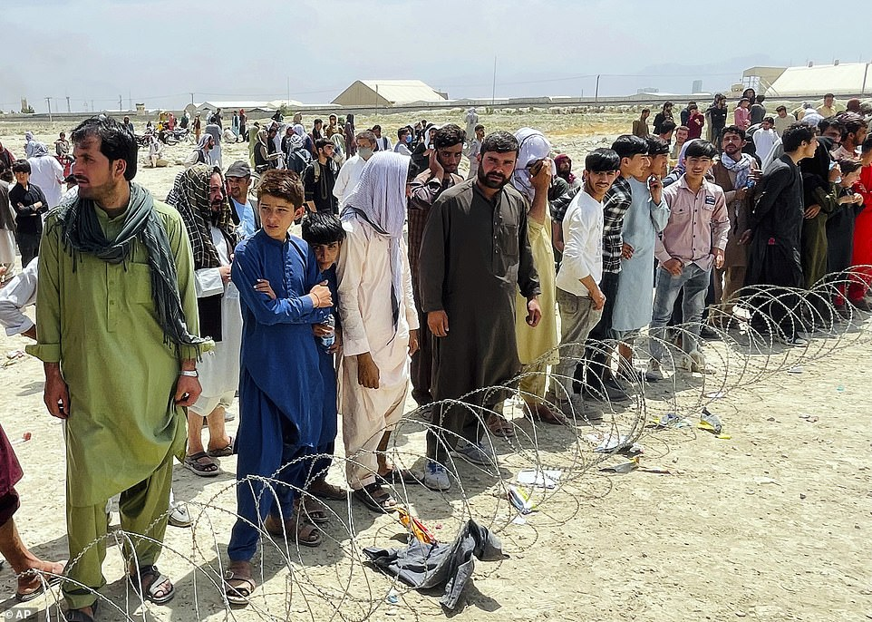 Hundreds of people gather outside the international airport in Kabul, Afghanistan on Tuesday