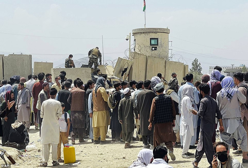 """Afghan security guards stand on a wall as hundreds of people gather outside the international airport in Kabul on Tuesday. The Taliban declared an """"amnesty"""" across Afghanistan and claimed civilians would be allowed safe passage to the airport"""