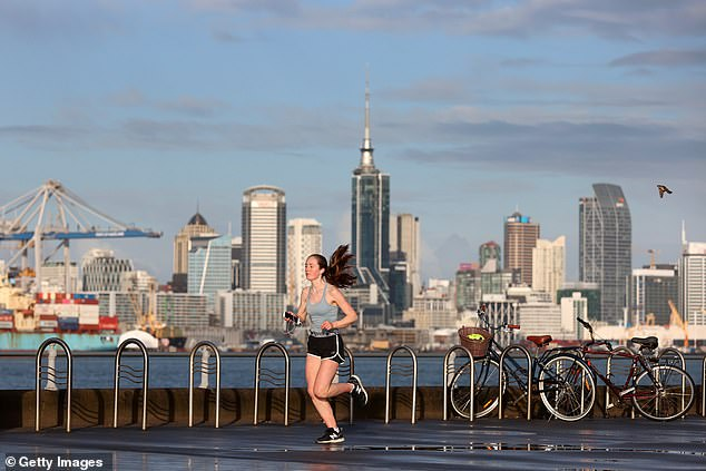 Level 4 Covid alert restrictions are in place across Auckland in New Zealand (pictured, a lone runner along the Devonport waterfront)