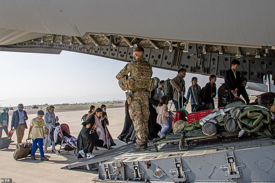 A British soldier stands guard as British citizens and dual nationals residing in Afghanistan are loaded on to an evacuation flight at Kabul Airport in an undated photograph