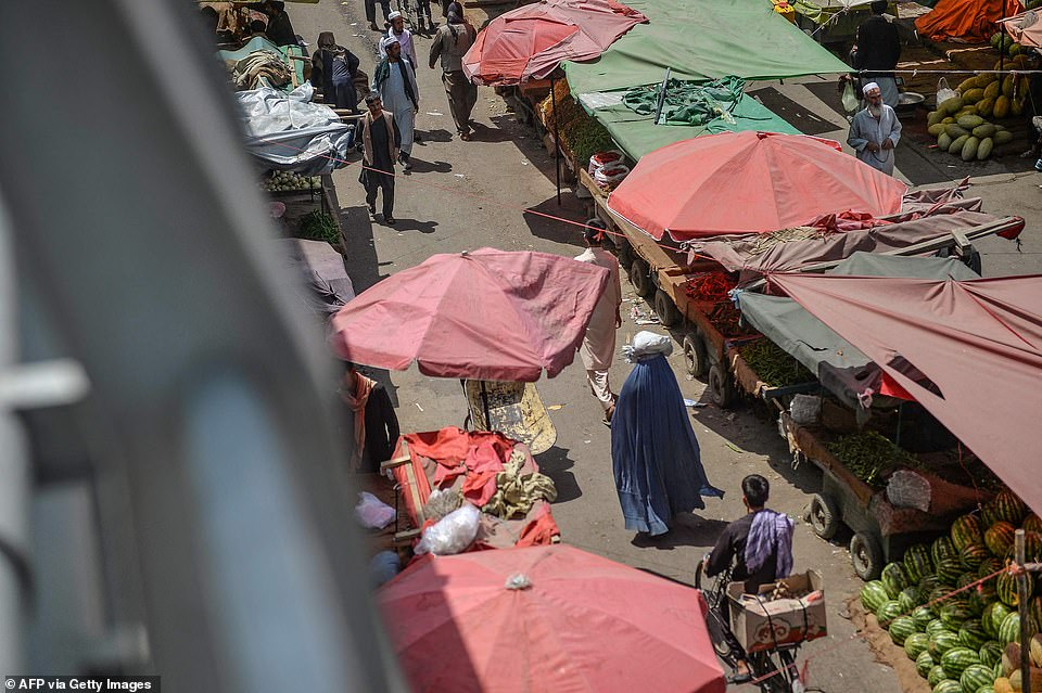 Civilians make their way around a market in Kabul - women with their heads covered and men wearing traditional dress - as the Taliban begins to reassert control over the country