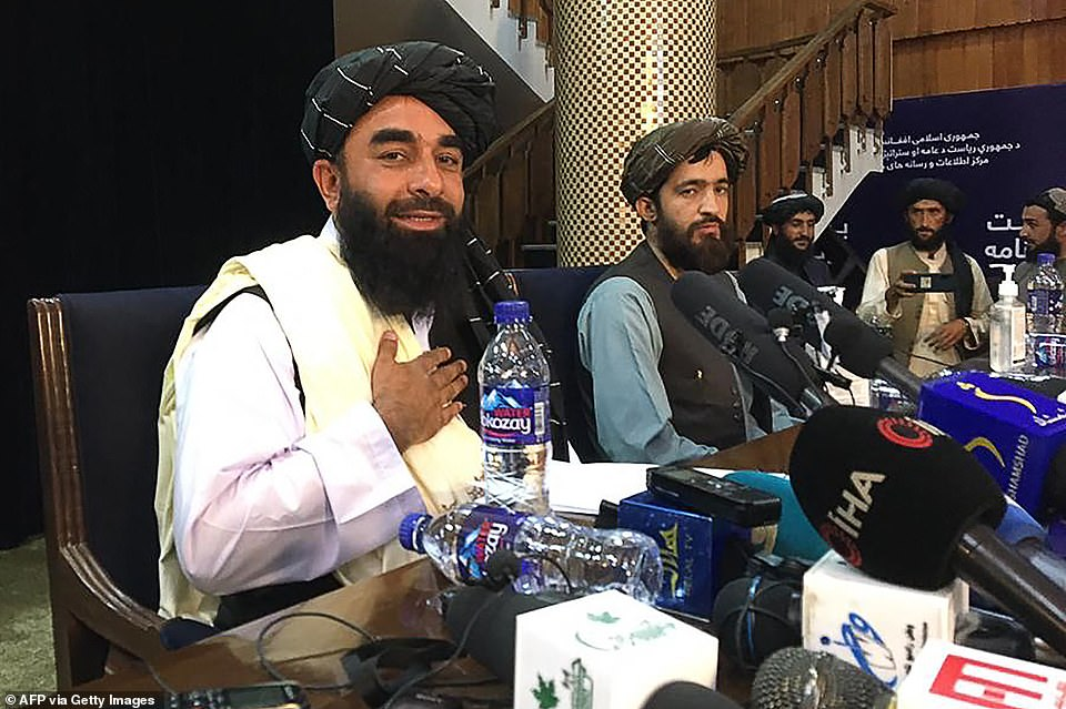 Taliban spokesperson Zabihullah Mujahid (L) gestures as he arrives to hold the first press conference in Kabul