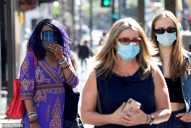 Pictured, people walking across Hollywood Boulevard wearing masks in March