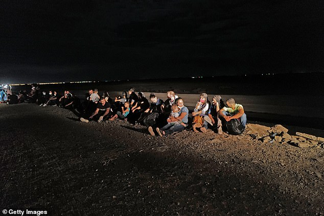 A group of migrants is detained by U.S. Customs and Border Protection Sunday night in San Luis, Arizona
