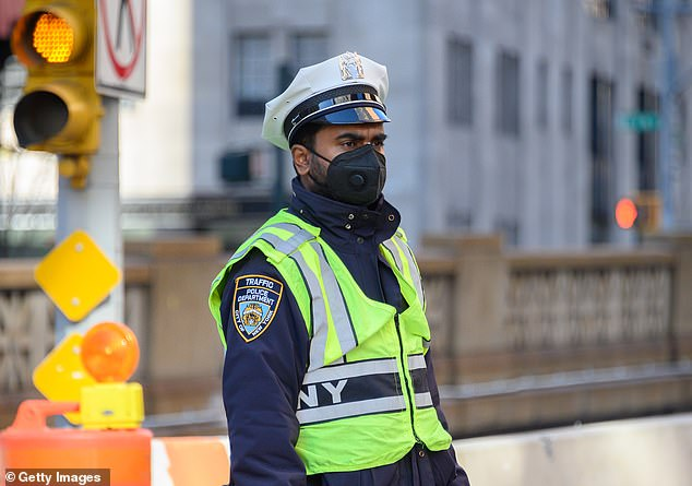 The NYPD will require unvaccinated cops to wear face masks both inside and outside in new rules. Above, an NYPD traffic enforcement agent wears a mask last March