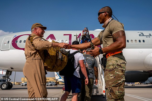 In this image released by the US Central Command Public Affairs, US Embassy personnel from Afghanistan board a Qatar Airways flight to Kuwait as part of Operation Allies Refuge on August 17, 2021, at Al Udeid Air Base, Qatar