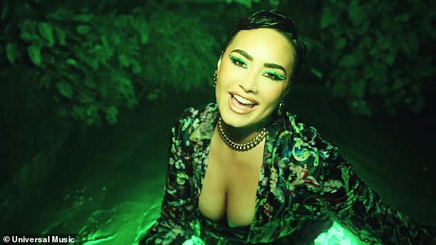 Glam:The aquatic look revealed the singer standing in a small pool of illuminated green water, wearing a beautifully patterned low-cut outfit with ample cleavage showing