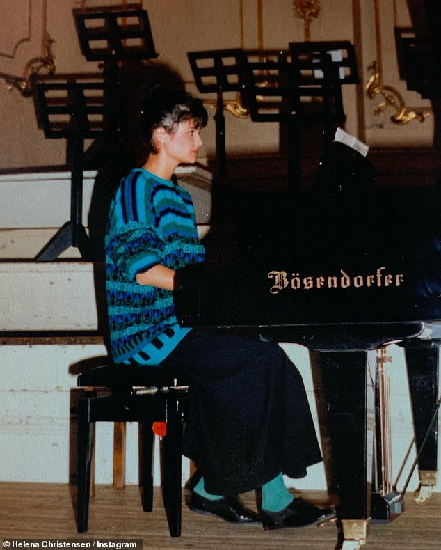 Talented: Sporting a a stripy blue sweatshirt, complete with an eye-popping pair of turquoise socks, the fashion icon sat in front of a grand piano during a school recital