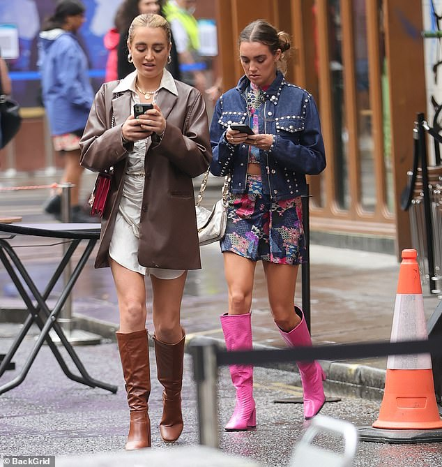 Strolling: Accessorising the dress with a delicate gold belt, the Love Island alum kept her arms dry amid the wet weather in an oversized brown leather collared-jacket