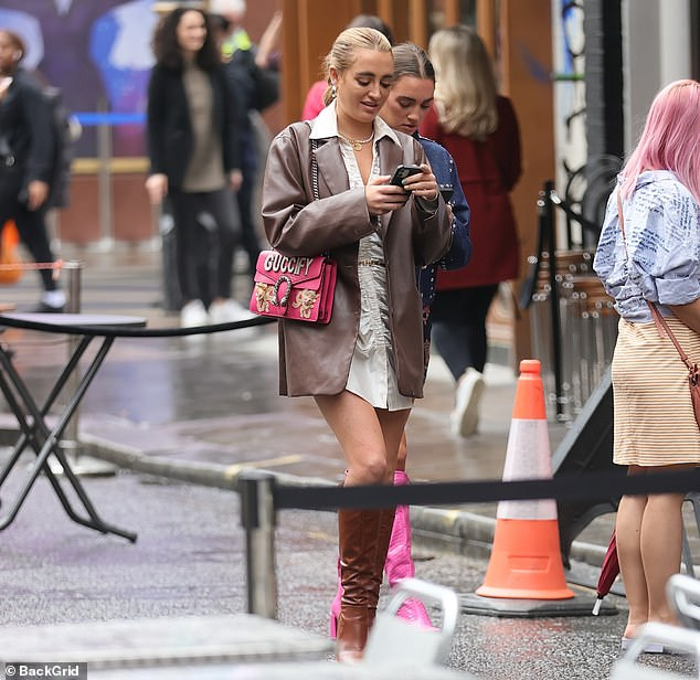 Showstopping: She had thrown a hot pink Gucci clutch over her shoulder and strutted her way through the Big Smoke in a pair of knee-high brown leather boots