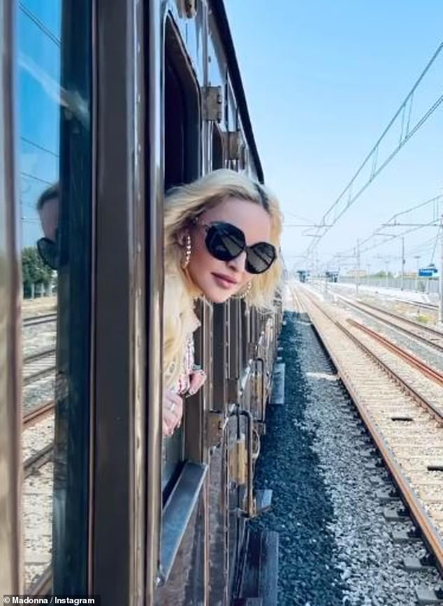 Ageless: Madonna looked more radiant than ever as she shared a snap of her poking her head out of a train window in large black glamorous glasses and gold hoop earrings