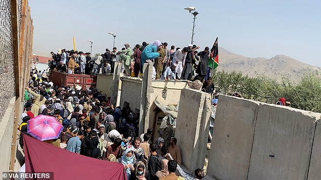 A still image taken from video shows crowds of people near the airport in Kabul, Afghanistan August 23. Biden suggested on Sunday that extending the US troop withdrawal deadline past August 31 isn't off the table