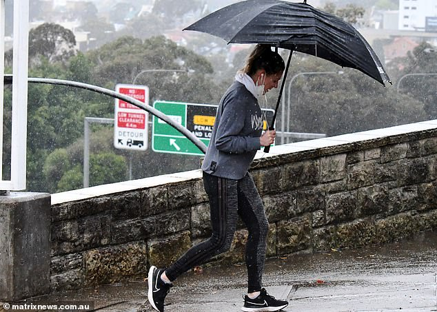 Weather experts have revealed some parts of Australia will see a wet start to spring, following patterns from winter (pictured a woman with an umbrella in Sydney's east)