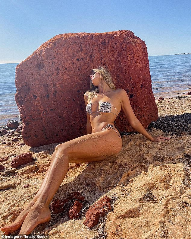 Don't move an inch!Posing against a rock on the beach, she also flaunted plenty of underboob in the strapless swimwear