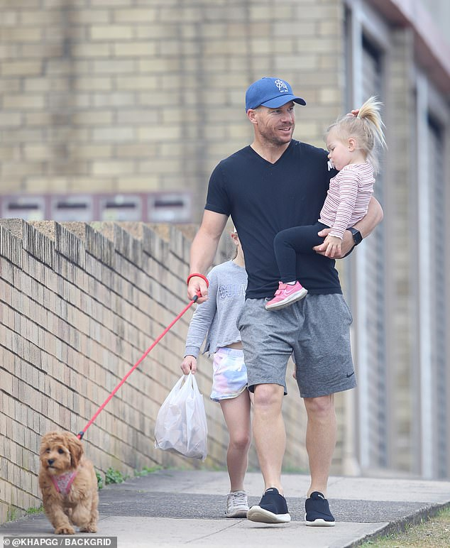 Puppy love! On Thursday, David Warner dedicate a sweet Instagram post to a special family member, their pet cavoodle, Cookie. Pictured, David out with his puppy and two daughters