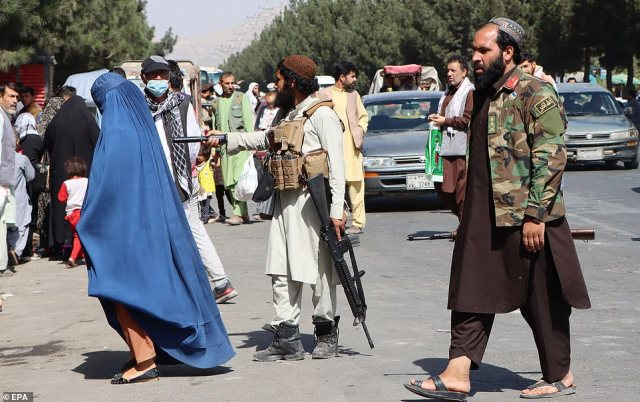 Taliban fighters stand guard as they block the road to Kabul airport on Friday, a day after the deadly blasts