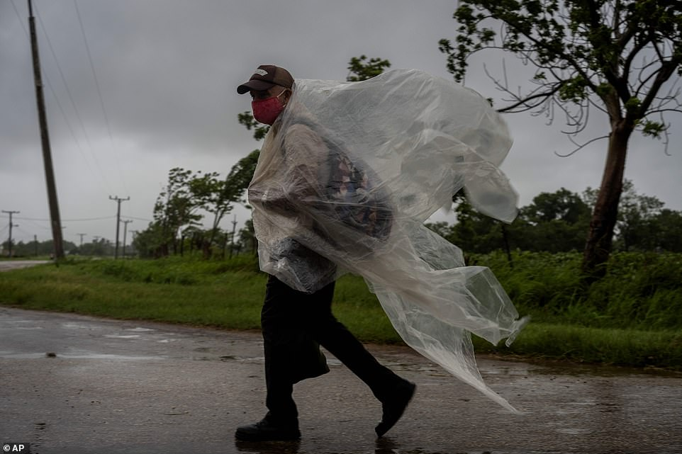A man using plastic against heavy rainfall caused by Hurricane Ida in Cuba on Friday walks on a road leading to Batabano in the Mayabeque province.After battering Cuba on Friday with 80 mile per hour winds, Ida began churning northwest this morning - it is expected to reach the US this Sunday, 16 years to the date of Hurricane Katrina's landfall in 2005