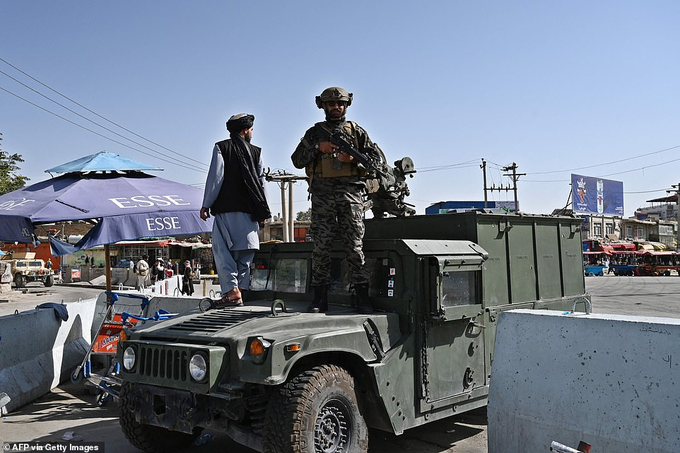 """A Taliban Badri fighter, a """"special forces"""" unit, stands guard on Humvee vehicle at the main entrance gate of Kabul airport in Kabul on Saturday, following the Taliban stunning military takeover of Afghanistan"""