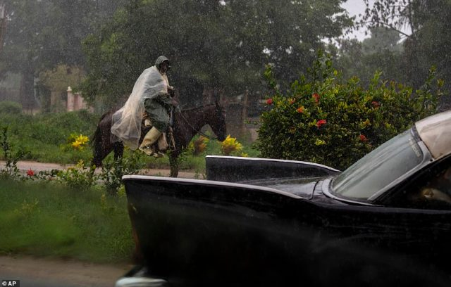 An man rides on horseback in Cuba along a road leading to Batabano in the Mayabeque province on Friday as Hurricane Ida whips 80MPH winds through the country's western tip