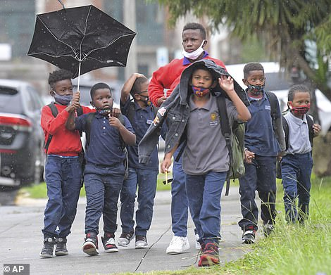 Children try to protect themselves from the rain near the Dryades YMCA in New Orleans, where a city-run sandbag distribution center is providing for queues of residents