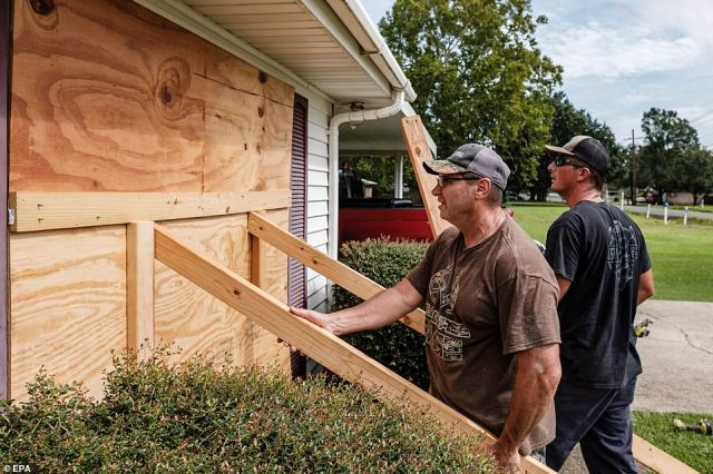 A St. Charles Parish man boards up his home on Saturday as Hurricane Ida approaches New Orleans. The storm is predicted to cause 'catastrophic' damage to infrastructure and buildings