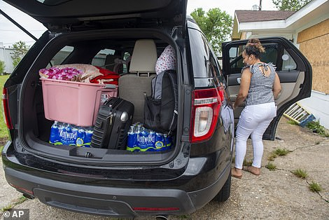 A New Orleans woman loads her car on Saturday as she and her family prepares to evacuate to Florida