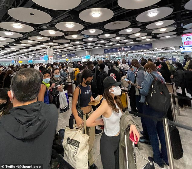Hundreds of holidaymakers were seen standing in close proximity to each other as they waited pass through checks at Border Control