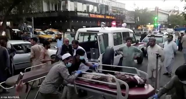 People are seen carrying an injured person to a hospital after an attack at Kabul airport on Thursday