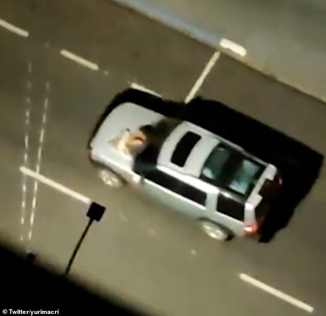 A civilian hostage strapped to the bonnet of a getaway car is driven through the streets of Araçatuba following a huge raid by dozens of gunmen