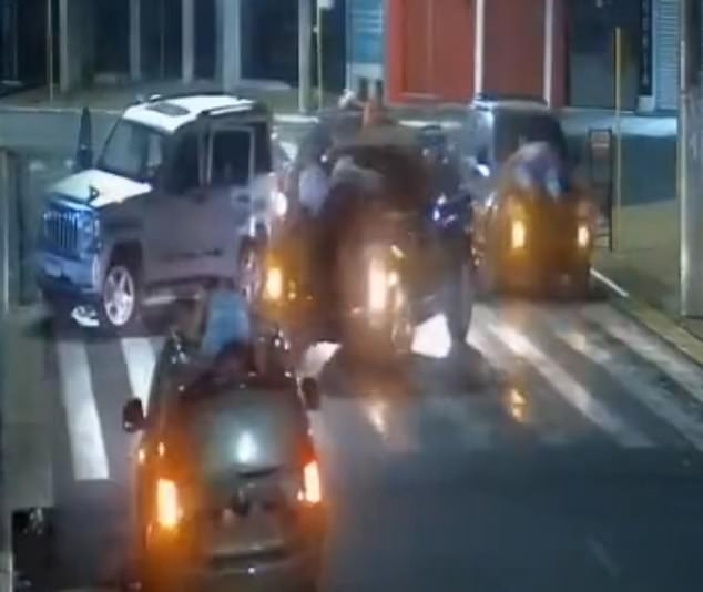 A convoy of cars with multiple people strapped to their bonnets and poking out their sun roofs turns around in the street as the bank robbers flee