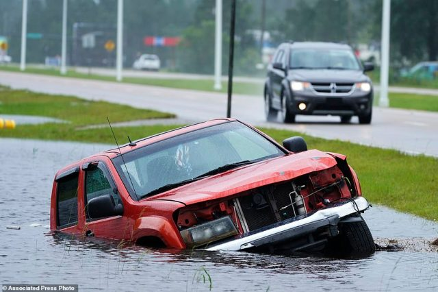 Many residents struggled to evacuate to safer locations, but others lacked the funds to do so and had to stay in their homes and hope for the best. Above, a car got stuck in the storm's floodwaters in Bay St Louis, Mississippi