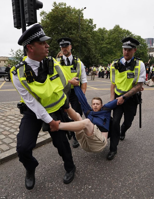 An XR activist being hauled away by three officers on Tower Hill, just yards away from Tower Bridge, during this afternoon's protest