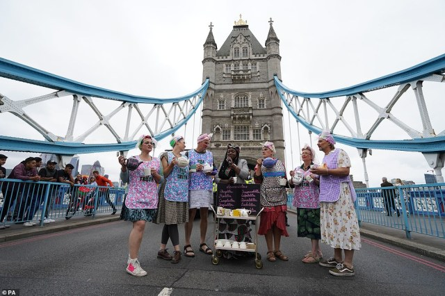 Extinction Rebellion activists dressed in floral aprons and dresses and pushing a tea tray stand on Tower Bridge today