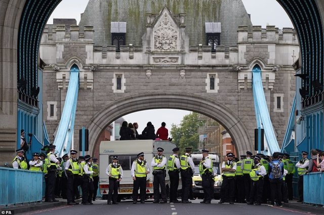 Dozens of Met officers formed a cordon around a caravan that Extinction Rebellion activists used to block Tower Bridge today