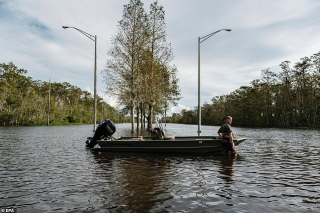 A man stands in a flooded street with a boat to assist in search and rescue missions related to flooding from Hurricane Ida in Jean Lafitte, Louisiana on Monday
