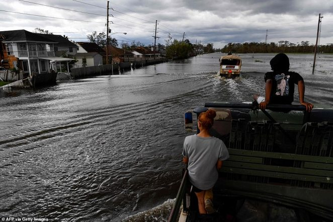 Catera Whitson (left) and Kyler Melancon (right) ride in the back of a high water truck as they volunteer to help evacuate people from homes after neighborhoods flooded in LaPlace, Louisiana on Monday