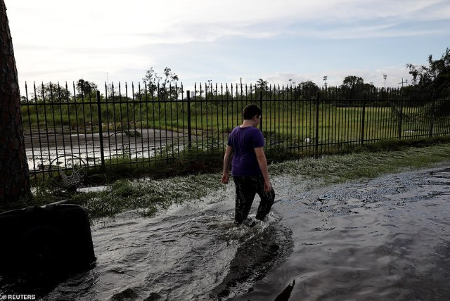 A boy walks in a flooded street in New Orleans on Monday - a day after Hurricana Ida tore through the region
